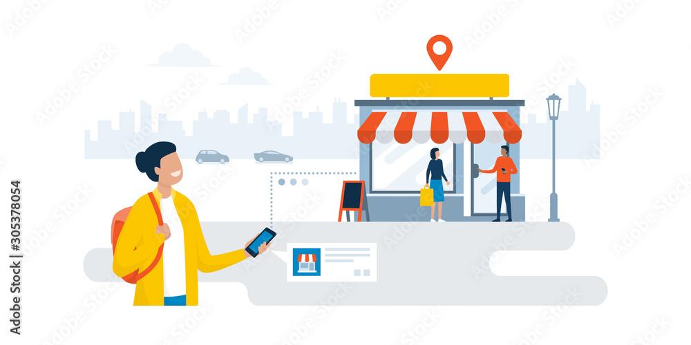 Fototapeta Woman finding a shop using her smartphone