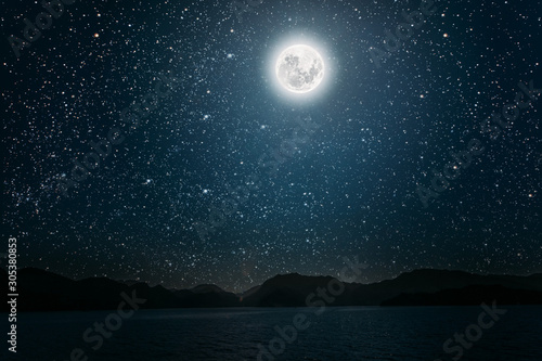 Fotografiet moon against a bright night starry sky reflected in the sea