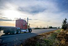 Big Classic Rig Red Semi Truck With Flat Bed Semi Trailer Running On The Evening Road With Sunset