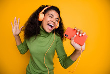 Photo Of Casual Curly Wavy Brown Haired Cheerful Cute Pretty Girlfriend Singing Into Telephone Microphone In Headphones Emotional In Green Sweater Isolated Vivid Color Background
