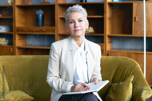 Attractive short haired middle aged female CEO sitting on comfortable couch in office interior writing in her notebook, checking appointment list, looking at camera with serious confident expression