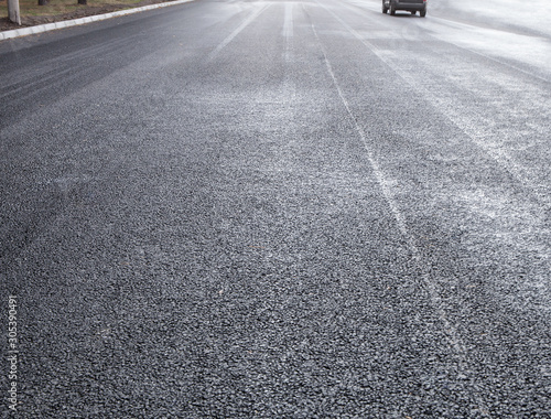 New asphalt on the road with a receding car in the background Canvas Print