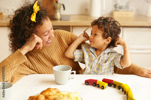Fényképezés Happy young curly haired female wearing sweater having breakfast in kitchen sitting at table with mug and pastry, watching her handsome adorable infant son play with toy railway