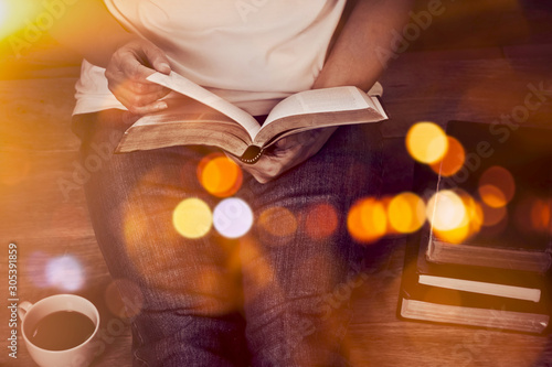Close up of woman hands hold and reading bible indoor near a cup of coffee and b Fototapete