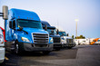 canvas print picture - Different big rigs semi trucks standing in row on the truck stop parking lot at evening time