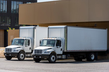 Small Compact Rigs Semi Trucks With Long Box Trailers Standing In Warehouse Dock Loading Cargo For Delivery