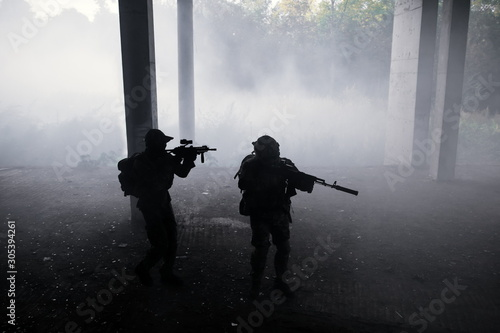 Photo Two military soldiers in camouflage with assault rifles storming enemies in the