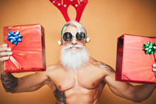 Happy Fit Senior Holding Christmas Presents - Hipster Older Man Having Fun Giving Gift Box During Xmas Holidays - Elderly Trendy People And Traditional Lifestyle Culture Concept