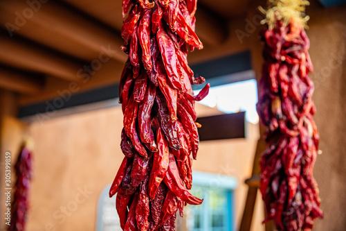Fototapeta premium Czerwona papryka chili suszone wiszące na wejściu do tradycyjnego budynku, Santa Fe w Nowym Meksyku