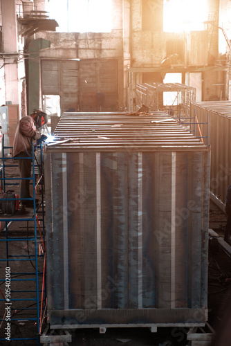 Photo  Welder collects a large metal container