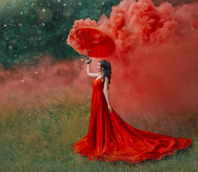 Woman In Red Silk Long Dress Train With Umbrella. Art Design Photography. Idea Creative Photo Shoot With Colored Smoke Bomb. Magical Light Nature. Glamorous Fashion Lady Walks In Woods. Valentines Day