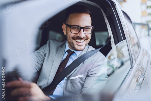 Fotografie, Obraz Cheerful caucasian businessman driving himself to work