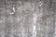 Gray concrete wall texture painted with white. The old white color that has been fading and peeling off. Texture of old dirty concrete wall for background.