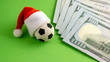Leinwanddruck Bild - A soccer souvenir ball with a Santa Claus hat next to one hundred US dollar bills. Green. The concept of Christmas betting, gifts and surprises for the new year or corruption and fraud in sports.