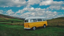 4K UHD Cinemagraph / Seamless Video Loop Of A Classic T2 Bulli Camper Van Standing On A Green Field On A Sunny Afternoon In England With Blue Sky, The Clouds Are Moving By Quickly.