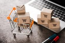 Selective Focus Of Toy Shopping Cart With Small Carton Boxes Near Laptop, E-commerce Concept