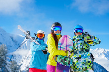 Sportsmen And Woman With Snowboard And Skis Standing On Snow Resort Against Background Of Mountain And Cloudy Sky