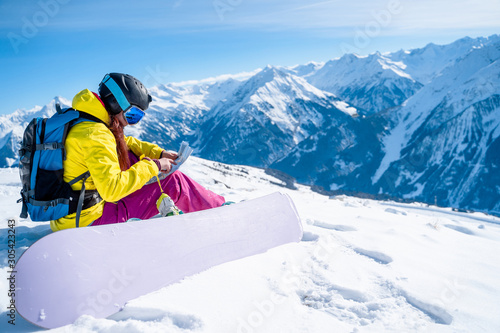 Fotomural Image of snowboarder girl in helmet with map in her hands sitting on mountain sl