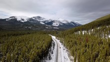 Aerial View As A Car Drives Along A Winter Road Surrounded By Pine Trees And Mountains