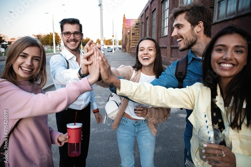 Fototapeta Group of friends stacking hands outdoor - Happy young people having fun joining and celebrating together obraz