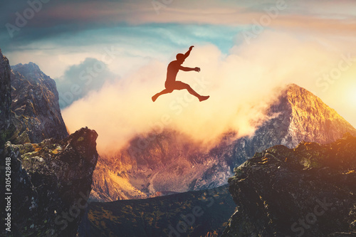 Foto Man jumping between mountains at sunset.