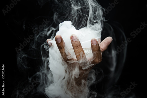 Cuadros en Lienzo Hand smoke from dry ice in a bowl, black background.