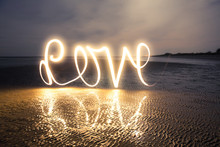 Light Painting Art: Writing Love With Light Into Darkness On The Beach At A Romantic Twilight