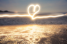 Romantic Light Painting : Heart Drawn With Flashlight At Blue Hour On The Beach Near The Water At Low Tide