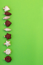 Christmas Composition. Christmas Glass Red Sparkling Decoration Cones, Hearts And Flowers On A Green Background.