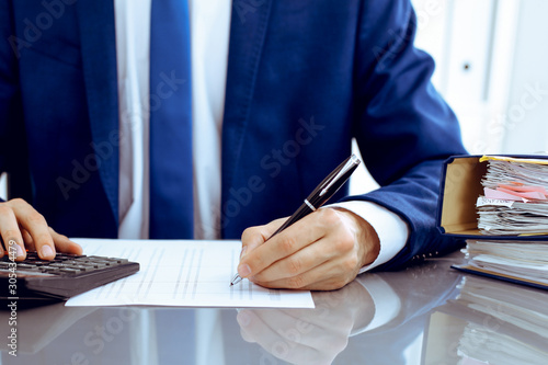 Fototapeta Bookkeeper or financial inspector hands making report, calculating or checking balance. Internal Revenue Service inspector man checking financial document. Business, tax and audit concepts obraz