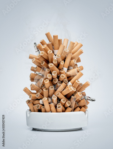 Photo Ashtray full of cigarettes isolated on gray background with copy space