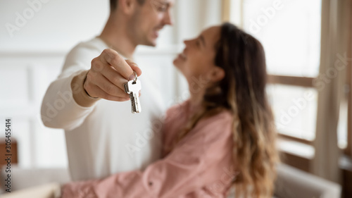 Poster de jardin Individuel Happy couple hugging holding keys buy new apartment concept, closeup