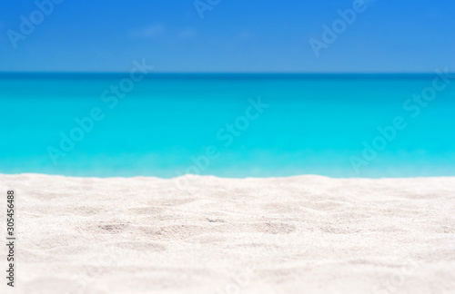 Foto auf AluDibond Turkis Close up of tropical sand with blurred sea and sky background, summer day. Sandy beach with blurry blue ocean copy space for product.