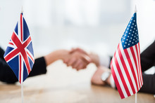Selective Focus Of Flags Of Usa And United Kingdom Near Diplomats Shaking Hands