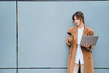 Young Beautiful Businesswoman In Coat With Laptop Confidently Using Cellphone Outdoor