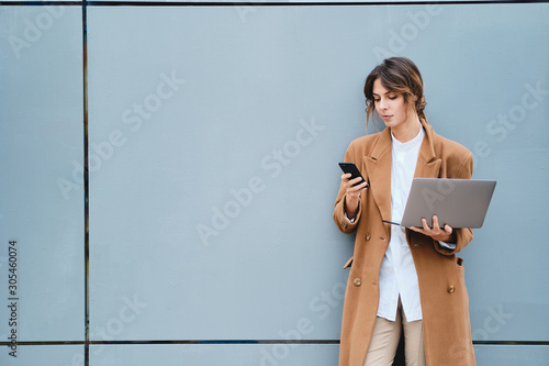 Fototapeta  Young beautiful businesswoman in coat with laptop confidently using cellphone ou