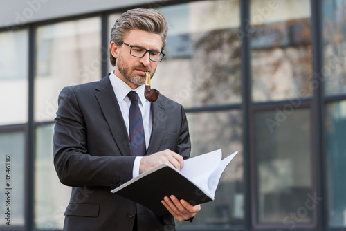 handsome diplomat smoking pipe and looking at folder with documents Wallpaper Mural