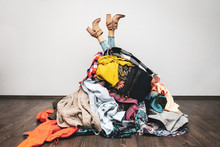 Woman Legs Out Of A Pile Of Clothes On The Floor. Shopping Addiction Concept