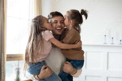 Fotografía Funny cute small daughters kiss happy daddy on cheeks