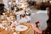 New Year 2020. New Year Mood. Table With A Gold Tablecloth, Decorated With Candles And Tableware For Celebration. Festive Still Life By Candlelight. Girl Holding A Sparkler. Close-up.