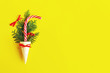 canvas print picture - Striped red and white Christmas cane and coniferous, fir or spruce branches in a waffle cone for ice cream on the yellow background. Creative, festive still life with food, flat lay, copy space