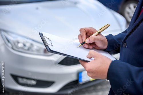 Leinwand Poster Male hands with clipboard against new car