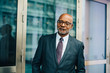 Portrait of confident senior businessman standing against glass door