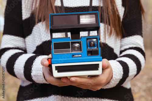 Photo Detalle de manos de mujer sujetando cámara de fotos instantánea de color azul