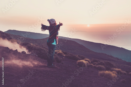 Foto auf Leinwand Aubergine lila Happy traveler woman viewed from back opening arms to hug the wonderful awesome nature during sunset time - enjoying the world and wanderlust lifetyle people - coloured jacket - happy travel people