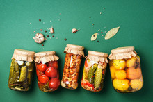 Canned And Preserved Vegetables In Glass Jars Over Green Background. Top View. Flat Lay. Copy Space.