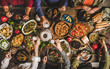 Traditional Turkish celebration dinner. Flat-lay of peopleeating Turkish salads, cooked vegetables, meze starters, pastries and drinking raki drink, top view. Middle Eastern cuisine