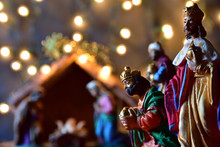 Christmas, Silhouette Of The The Three Wise Kings. Blurred Background Of The Nativity Of Jesus, Scene Of Bethlehem With The Holy Family And Small Night Lights Surrounding Them. Frontal Vision.