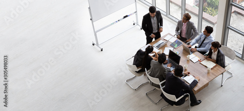 Obraz Top view of group of multiethnic busy people working in an office, Aerial view with businessman and businesswoman sitting around a conference table with blank copy space, Business meeting concept - fototapety do salonu