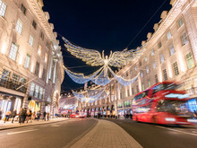 Angelic Decorations Illuminated And Red Double Decker Bus In Motion On Regents Street Of London In Chrtistmas Holiday, England